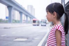 等待公共汽车的亚裔中国小女孩 免版税库存照片