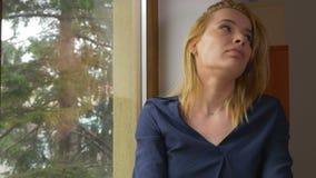 等待和看窗口的年轻可爱的乏味妇女 影视素材