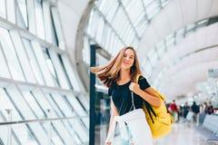 等待国际航班的青少年的女孩在机场离开终端 库存照片