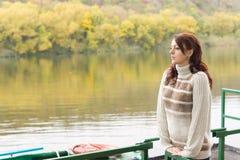 等待在一条平静的河的少妇 图库摄影