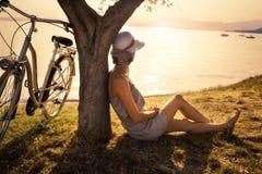 等待在一棵橄榄树的下爱的美丽的妇女在日落 库存照片