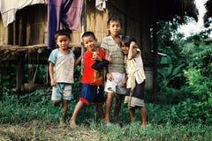 等待在他们的竹小屋样式家外面的孩子 免版税库存图片