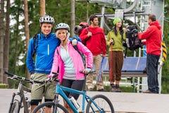 在升降椅以后的登山车夫妇和远足者 库存照片