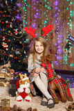 等待在圣诞节装饰的小女孩一个奇迹 免版税库存照片