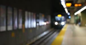 等待在地铁平台4k的被弄脏的通勤者火车 股票录像