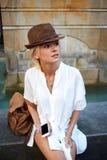 等待在她的手机的时髦的行家女孩电话在夏天周末期间国外 图库摄影