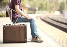 等待在带着一个减速火箭的手提箱的一个火车站的偶然旅客游人 免版税库存图片