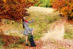等待在带着她的手提箱的一条乡下公路的女孩 库存照片