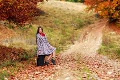 等待在带着她的手提箱的一条乡下公路的女孩 免版税库存图片