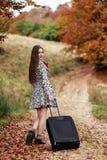 等待在带着她的手提箱的一条乡下公路的女孩 免版税库存照片