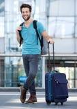 等待在有手提箱和袋子的机场的年轻人 免版税库存图片