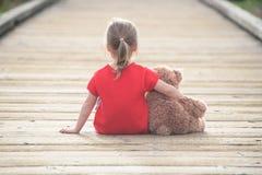 等待在木板走道的一件红色礼服的小女孩拥抱teddyb 免版税库存照片