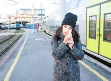 等待在火车旁边和抹她的逗人喜爱的女孩泪花 免版税库存图片