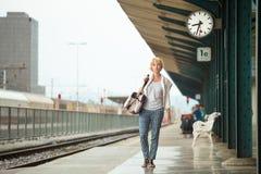 等待在火车站轴承葡萄酒书包平台的妇女  免版税库存图片