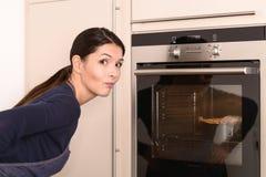 等待在烤箱的俏丽的妇女 库存照片