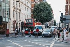 等待在牛津街,伦敦,英国的骑自行车者、汽车和公共汽车绿灯 免版税图库摄影