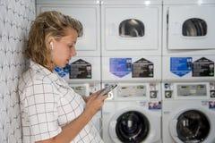 等待在自已服务洗衣店的白种人妇女 免版税库存照片
