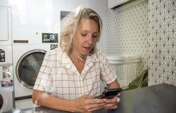 等待在自已服务洗衣店的白种人妇女 库存照片