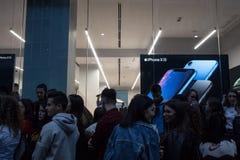 等待在苹果零售店窗口前面的人们新的苹果计算机智能手机,Iphone XR的发射,在黄昏 免版税库存照片
