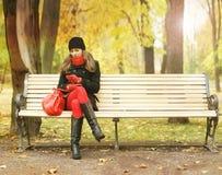 等待在长凳的一个少妇在公园 免版税库存图片