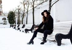 等待在长凳的年轻人相当现代行家女孩在冬天单独雪公园,生活方式人概念 库存照片