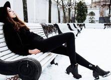 等待在长凳的年轻人相当现代行家女孩在冬天单独雪公园,生活方式人概念 免版税库存照片