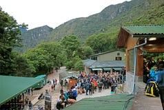 等待在马丘比丘印加人城堡,库斯科,秘鲁入口门的大小组访客  库存图片