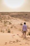 等待太阳下来在迪拜的沙丘的游人 库存照片