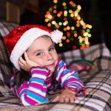 等待奇迹的圣诞节帽子的愉快的儿童女孩 库存照片