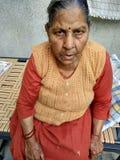 等待她的孩子的微弱的老妇人带来她的医学 库存照片