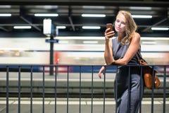 等待她的每日到站列车的女性通勤者 库存照片