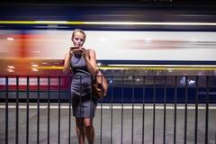 等待她的每日到站列车的女性通勤者 免版税库存图片
