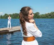 等待她的男朋友的女孩 拿着有稀土的人小船 库存图片