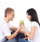 等待婴孩和吃健康食物的一对愉快的夫妇 免版税库存图片
