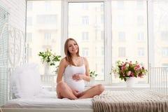 等待孩子的肉欲的孕妇坐在瑜伽姿势 免版税图库摄影