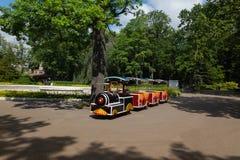 等待它的小乘客的小儿童的火车在公园 图库摄影