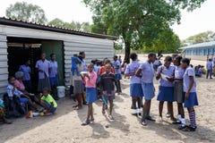 等待教训的愉快的纳米比亚小学生 免版税库存照片