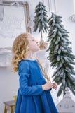 等待新年和圣诞节的孩子 有一个金分支的逗人喜爱的女孩在礼物她的手梦想  图库摄影