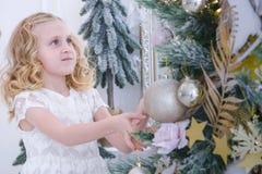 等待新年的孩子 装饰圣诞树的逗人喜爱的小女孩 图库摄影