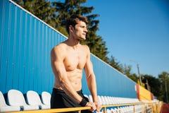 等待某人的赤裸上身的英俊的男性运动员在体育场户外 库存图片