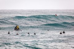 等待波浪日落海滩的冲浪者 免版税库存照片