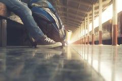 等待火车在火车站和飞行为下次旅行的旅客佩带的背包 免版税图库摄影