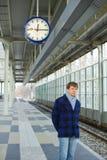 等待火车的一个人在时钟下 库存图片