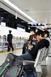 等待火车的乘客人群在驻地的平台 免版税库存图片