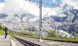 等待瑞士铁路的亚裔妇女从克莱茵沙伊德格训练在Wengernalp驻地有美丽的庄严瑞士阿尔卑斯看法  免版税库存照片