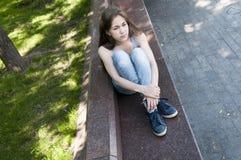 等待电话的年轻可爱的女孩坐长凳 在公园空白夏天的结构树的云彩 照片 库存图片