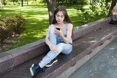 等待电话的年轻可爱的女孩坐长凳 在公园空白夏天的结构树的云彩 照片 免版税库存图片