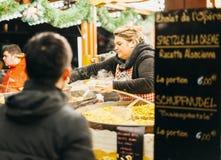 等待的人从市场摊位接受食物在圣诞节m 免版税库存照片