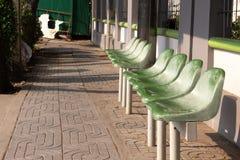 等待的公共汽车的绿色椅子在公交车站驻地 免版税库存照片