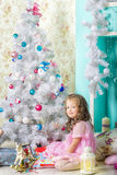 等待的圣诞节:小女孩装饰圣诞树 库存照片